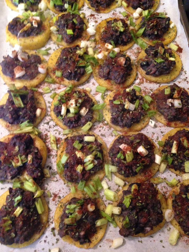 Polenta rounds topped with refried black beans, taco seasoning, green onions, and cilantro.