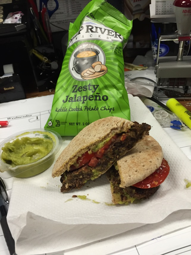 Spicy Zucchini and Black Bean burger with sliced tomato and guacamole.